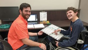 teenage blind boy in wheelchair using a modified keyboard with help of teacher