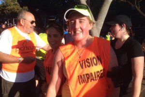 lady runner with orange vest with vision impaired on it