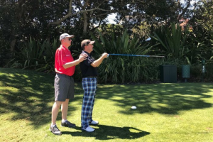 blind golfer with caddy behind postitioning him in direction to hit ball